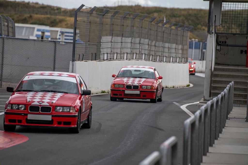 2 circuitautos komen de pitstraat in